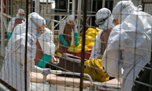 British health workers help an Ebola patient in Freetown, Sierra Leone. Photograph: Baz Ratner/Reuters